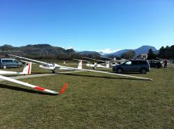 gliders, people, vehicles, sky, clouds, aircraft